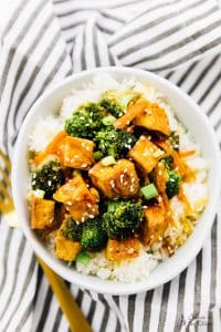 tofu and broccoli and carrots in a stir fry on top of a bed of rice