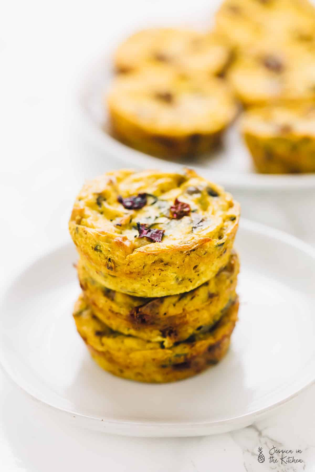 Three vegan quiche muffins stacked on a plate.