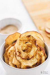 Cinnamon apple chips in a bowl, with sauce in the background.