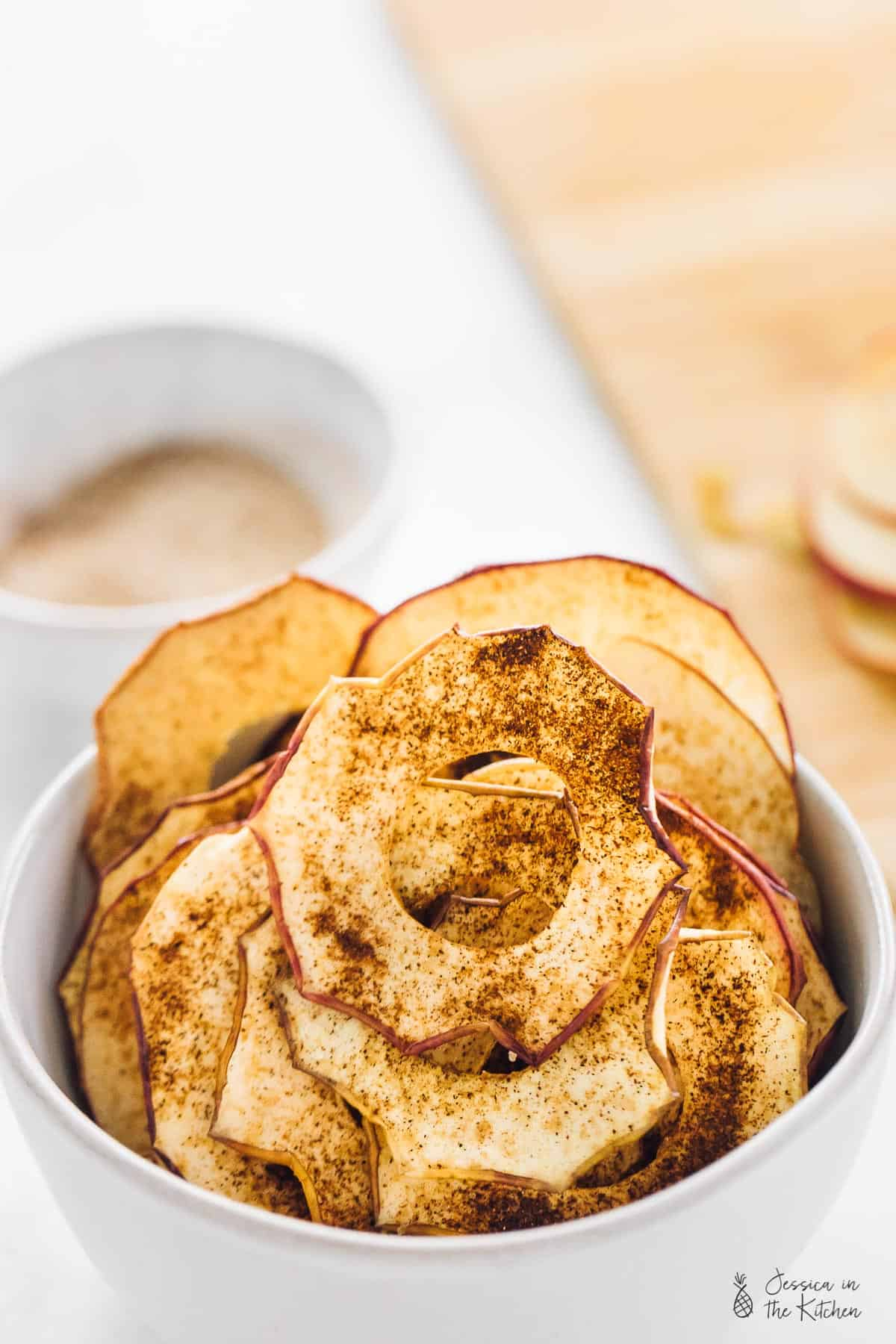 Cinnamon apple chips in a white bowl.