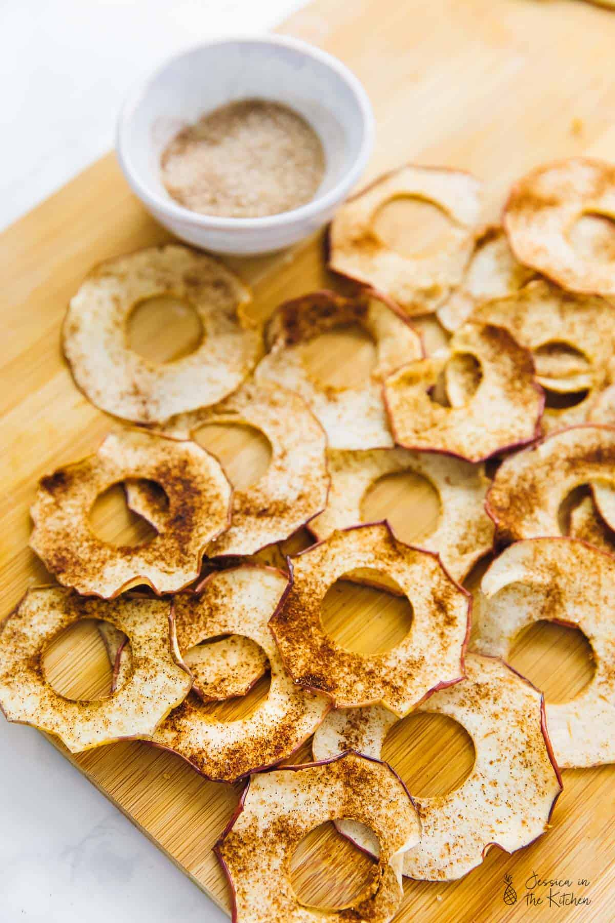 Overhead view of cinnamon apple chips on a wooden chopping board.