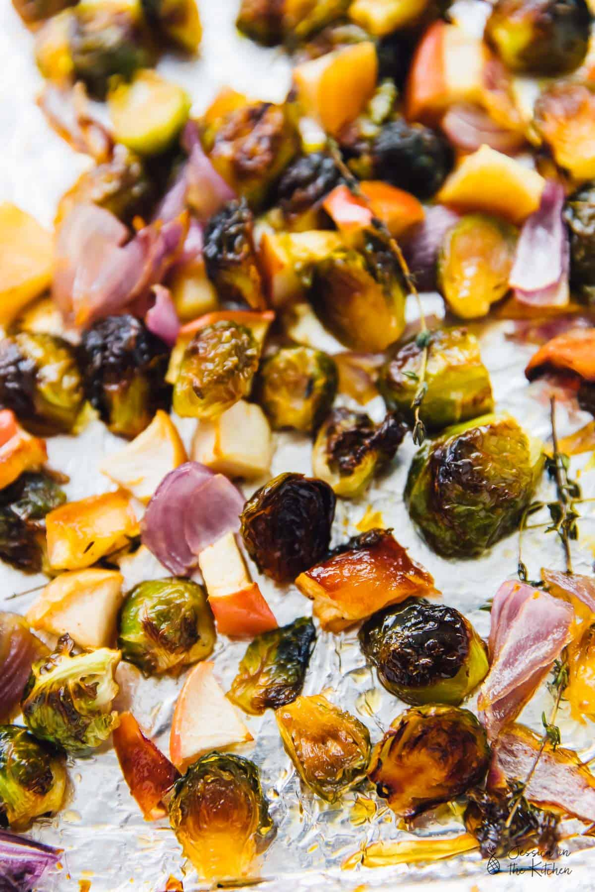 Maple roasted brussels sprouts with apples and pecans on a baking sheet.