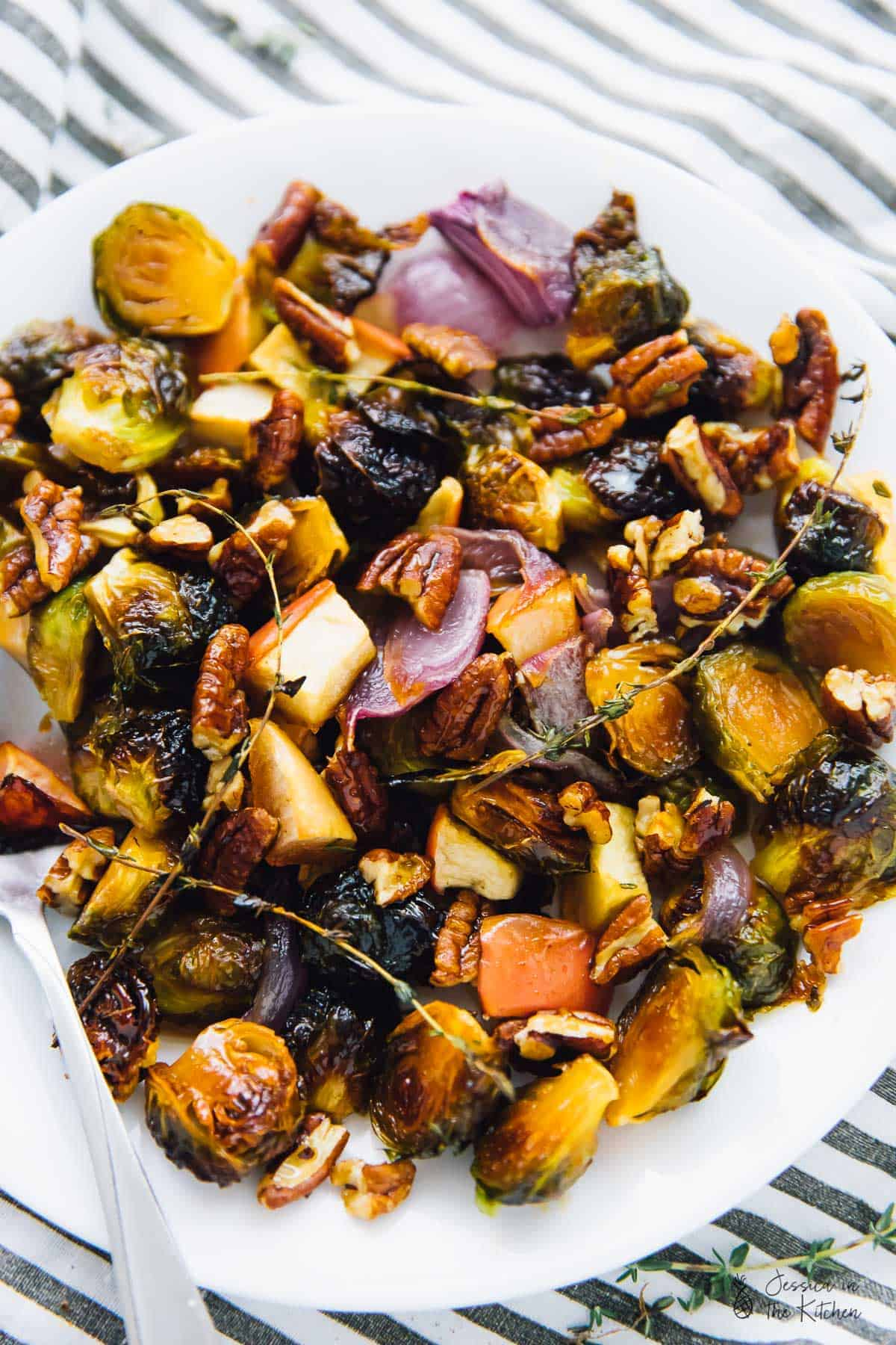 Top down view of roasted brussels sprouts with apples and pecans on a white plate, with a spoon on the side.