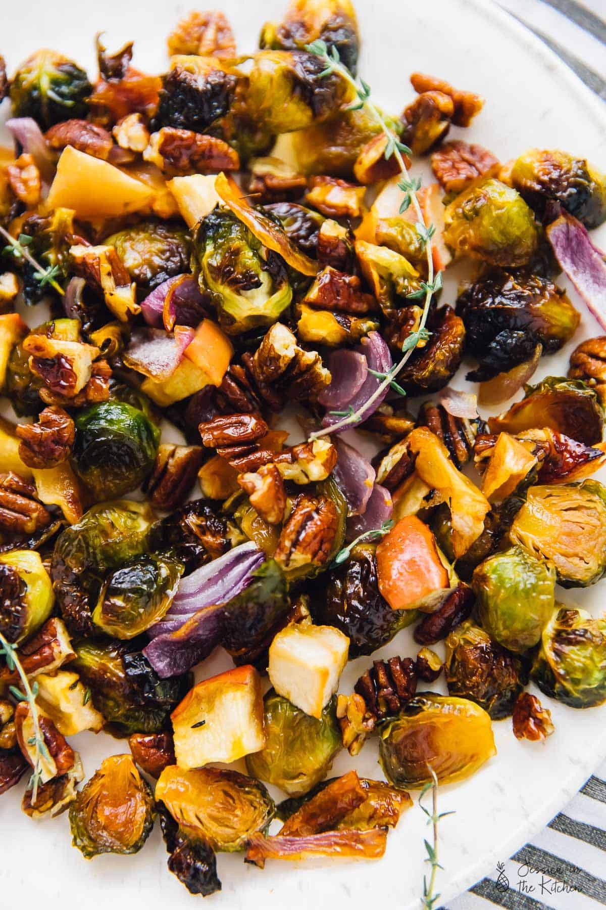 Top down view of maple roasted brussels sprouts with apples and pecans, on a big white plate.