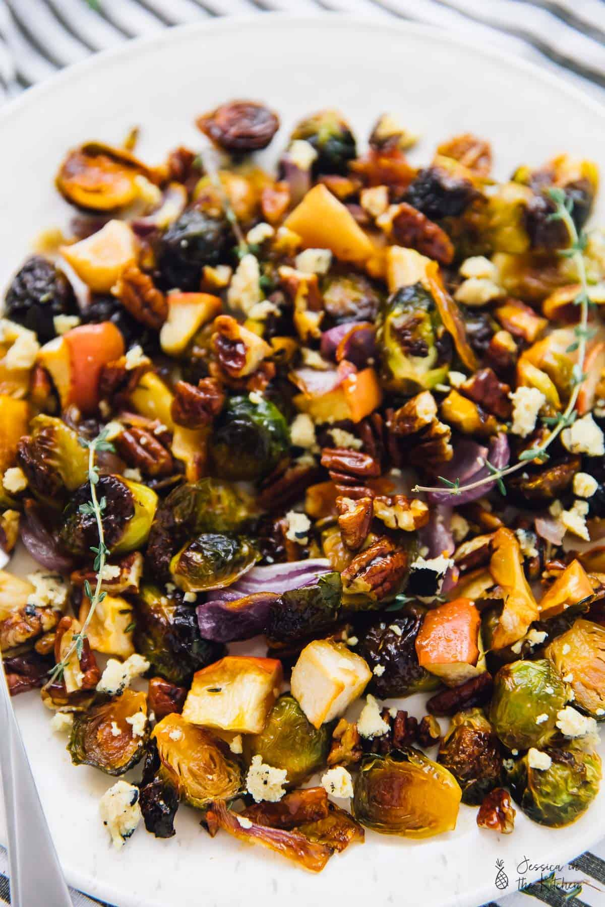 Roasted brussels sprouts with apples and pecans, topped with herbs, on a white plate.