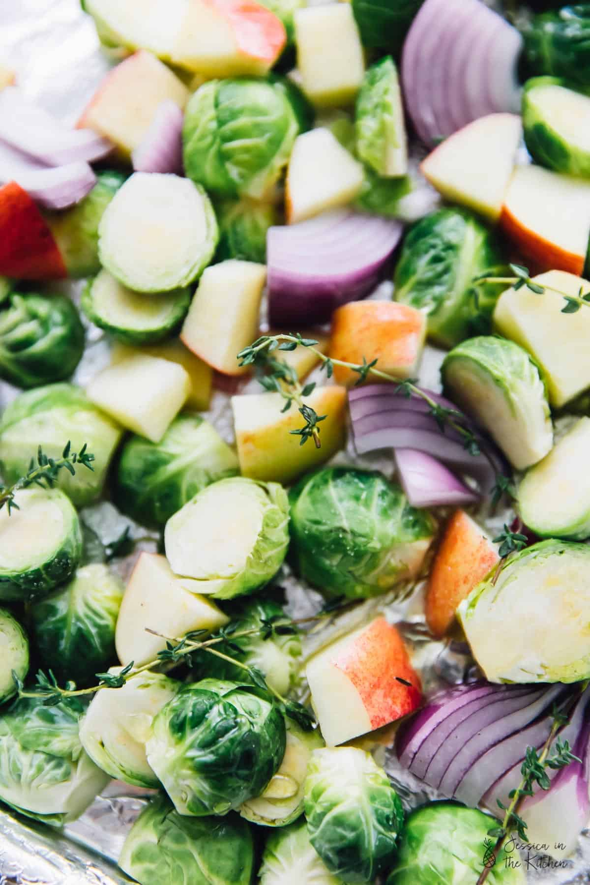 Top down view of brussels sprouts, apples and herbs, before roasting.