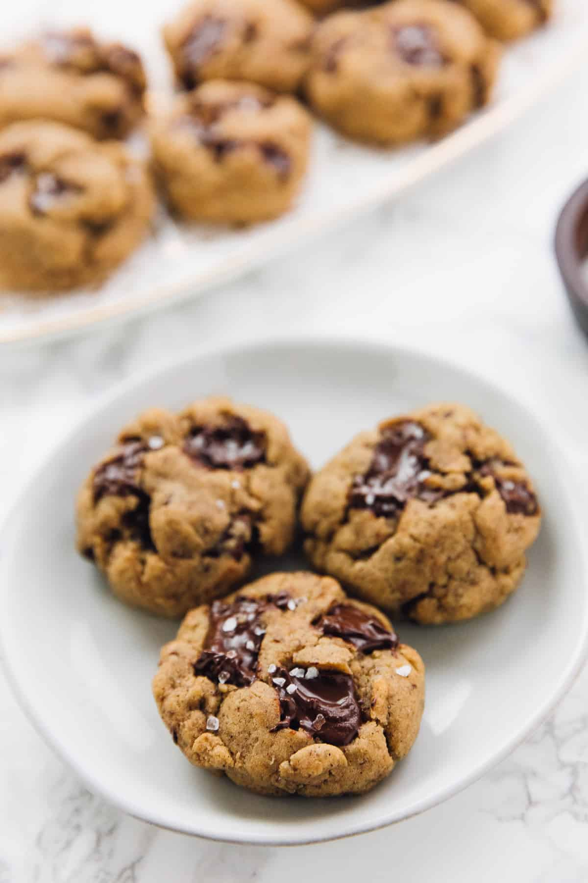 3 Salted chocolate chip tahini cookies on a plate with other cookies in the background
