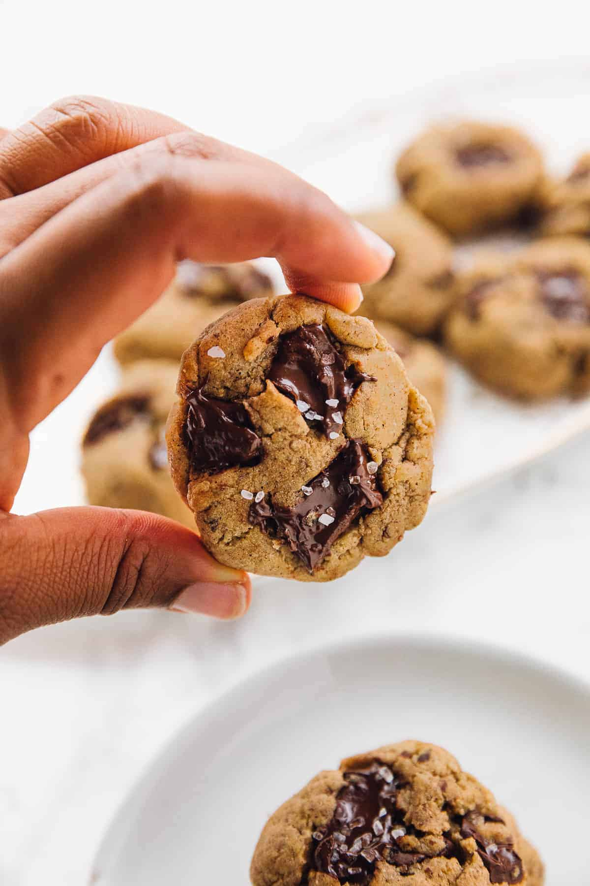 holding a Salted chocolate chip tahini cookie