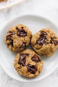 3 Salted chocolate chip tahini cookies on a plate close up
