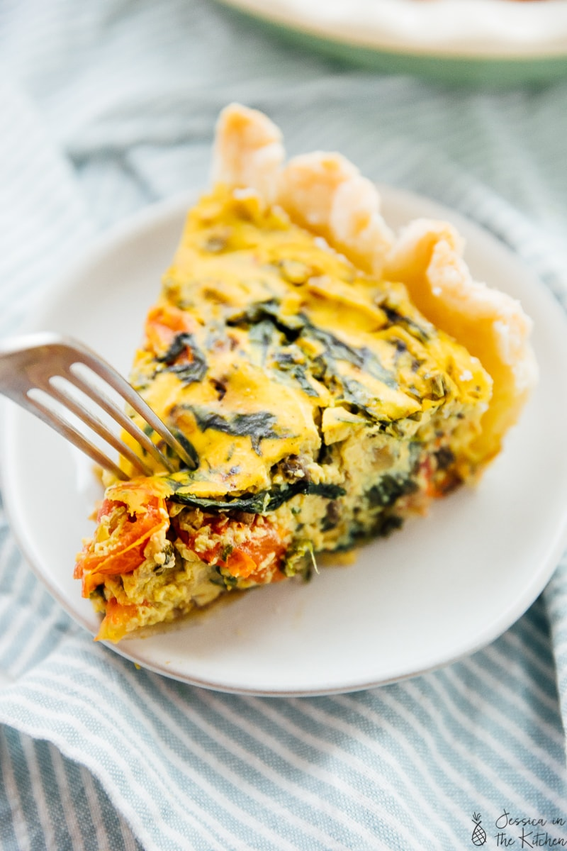 A fork digging into a slice of vegan quiche.