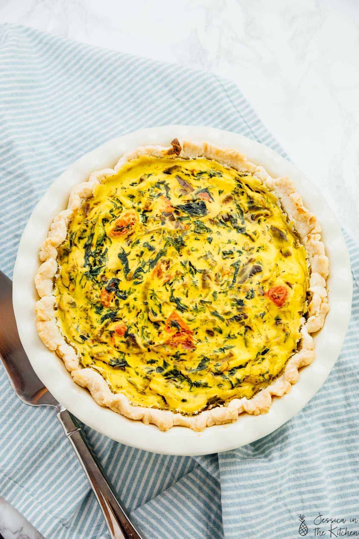 This Easy Vegan Quiche is perfect for your breakfast or brunch! The filling, made with tofu, is loaded with burst tomatoes, caramelised onions and sautéed mushrooms and spinach and is baked in a buttery flaky crust! via https://jessicainthekitchen.com
