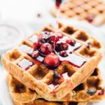 Syrup being poured onto orange cranberry waffles.
