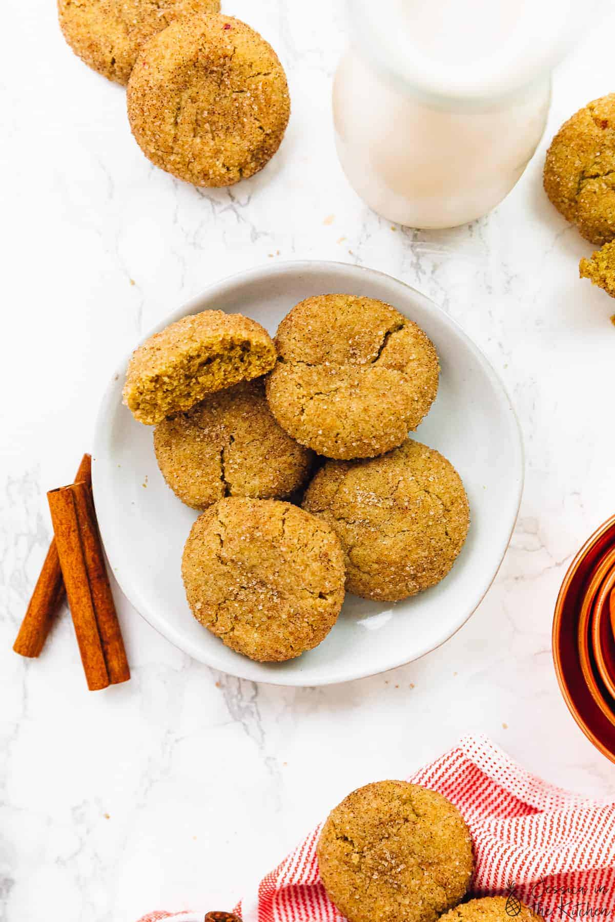 Five snickerdoodle cookies on a plate spread out with cinnamon sticks on the side.