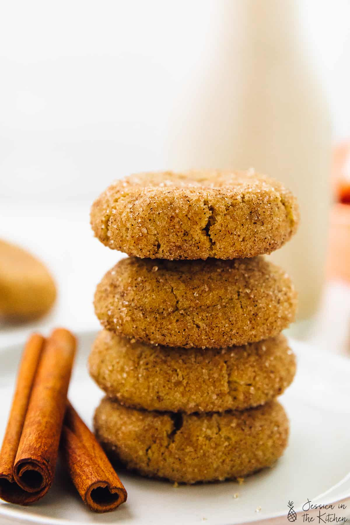 Snickerdoodle cookies in a stack of four on a plate with cinnamon sticks.