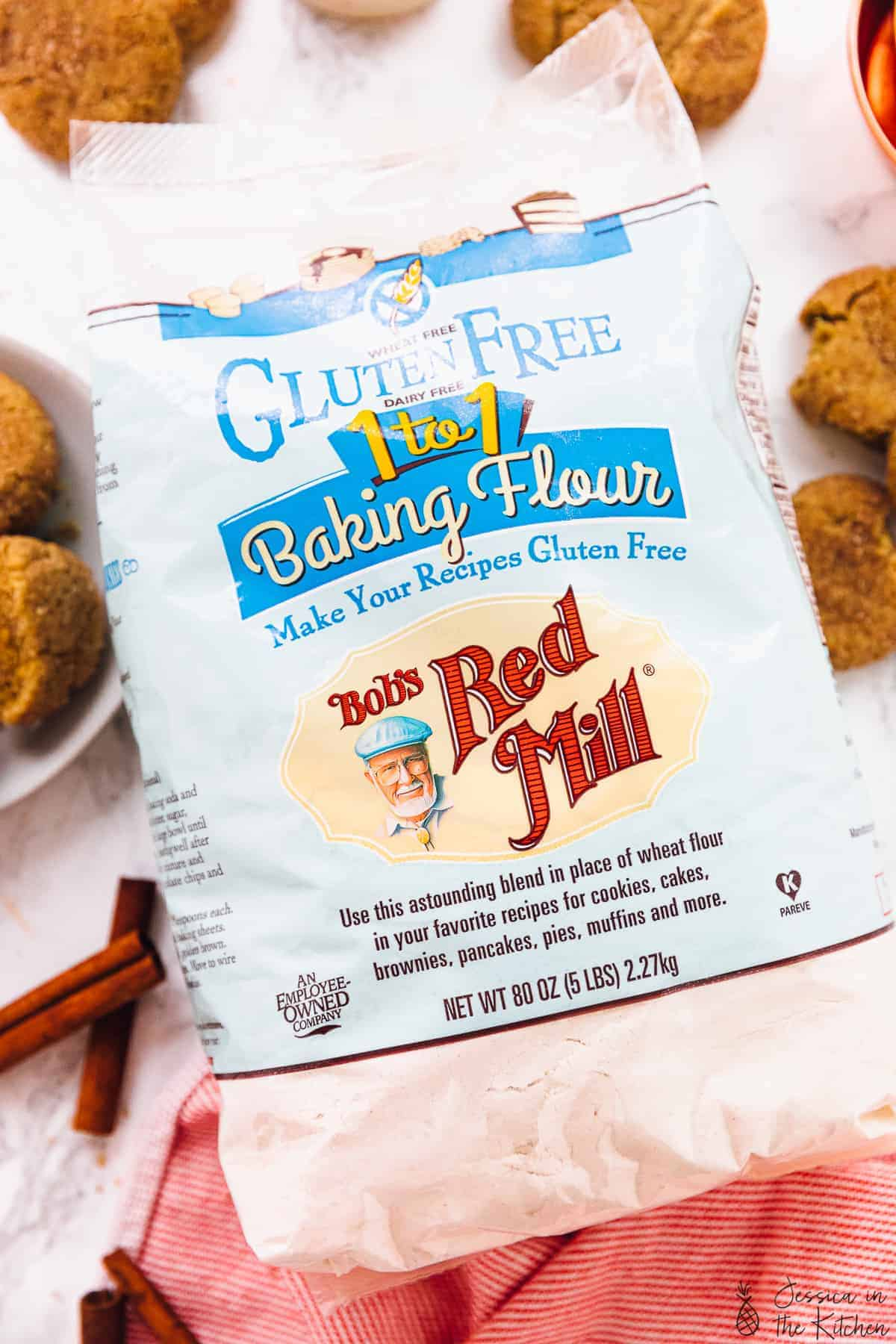 Bob's Red Mill Gluten Free Flour surrounded by cookies and cinnamon sticks.