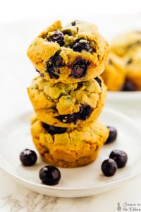 Blueberry muffins stacked on a plate, with loose blueberries on the side.