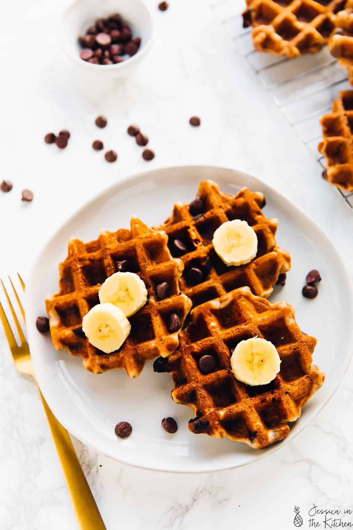 Overhead view of three banana bread waffles on a plate with a gold fork on the side.