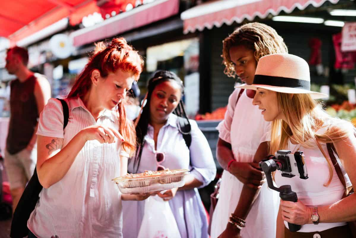 Four women at an open air market, looking at food.