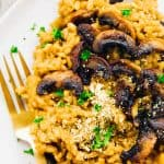 Mushroom risotto garnished with parsley, on a plate.