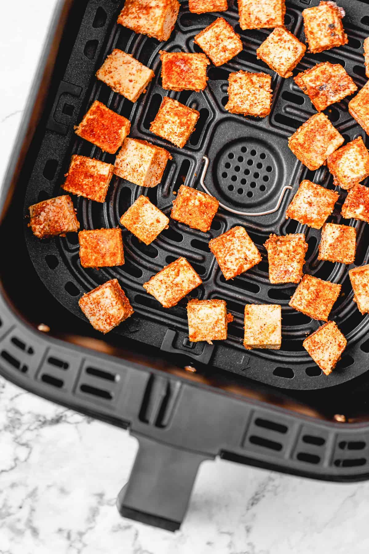 seasoned tofu cubes unbaked in an air fryer tray