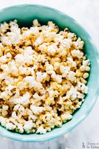 A bowl of cheesy popcorn in a blue bowl.