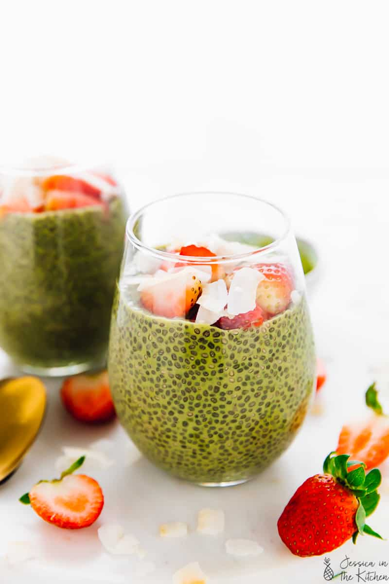 Two glasses of matcha chia pudding, topped with strawberries and coconut flakes.