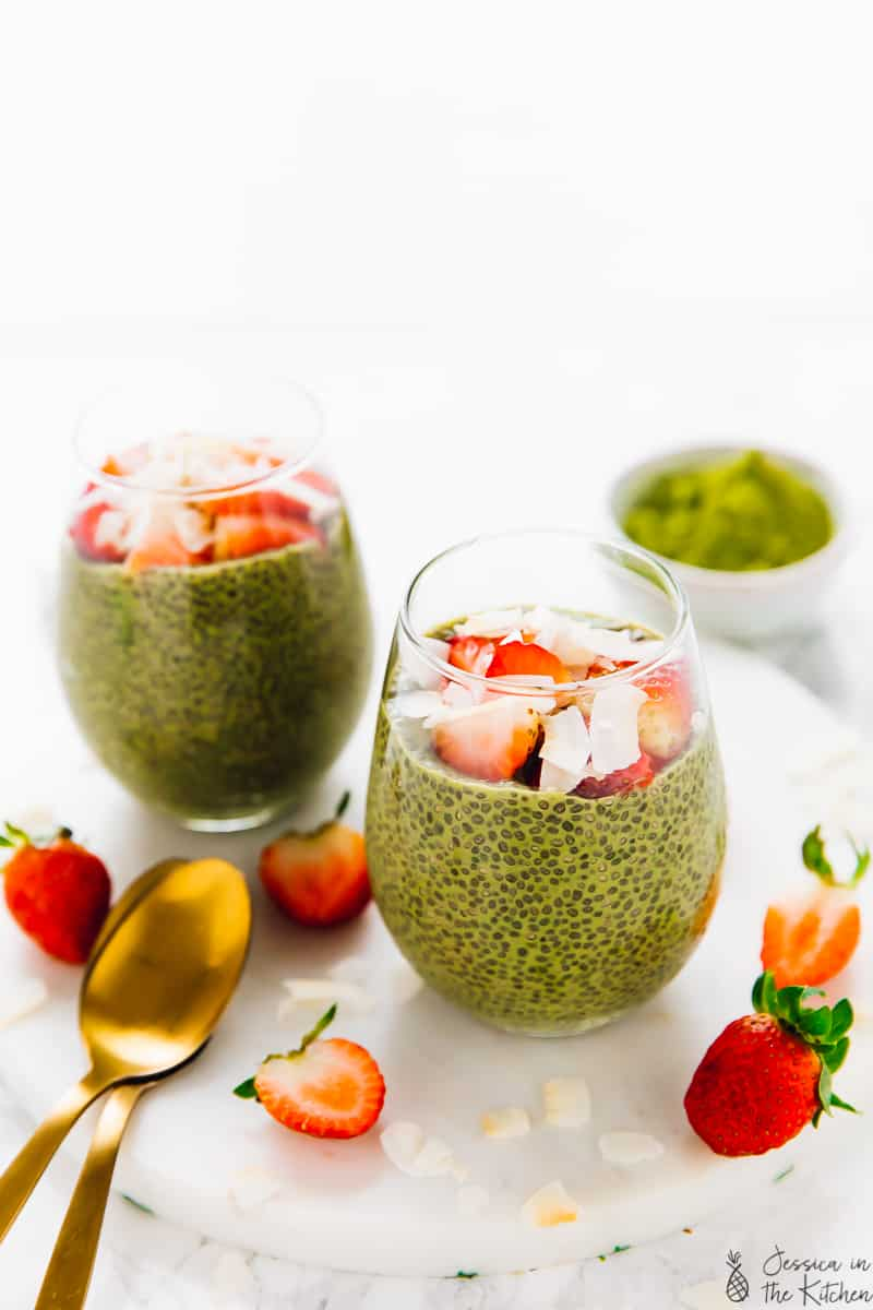 Two matcha green tea chia puddings on a white marble cutting board, surrounded with strawberries. The chia puddings are topped with chopped strawberries and large coconut flakes.