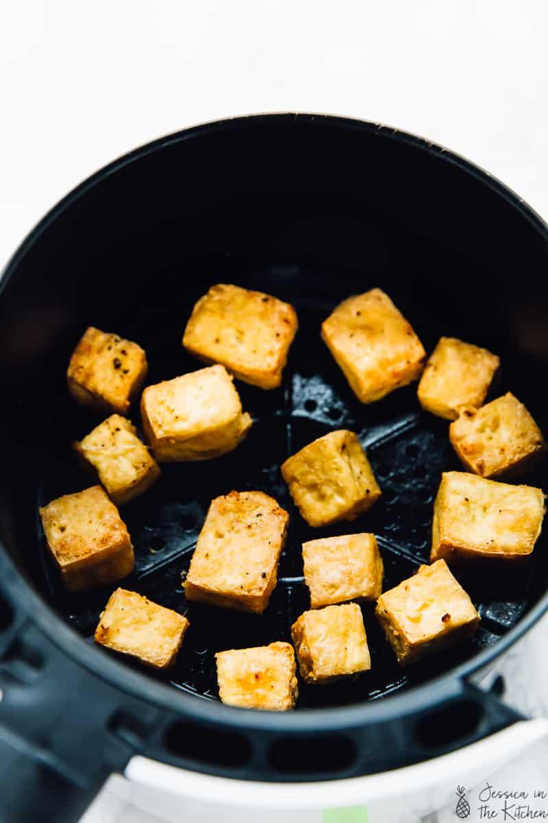crispy tofu in an air fryer basket