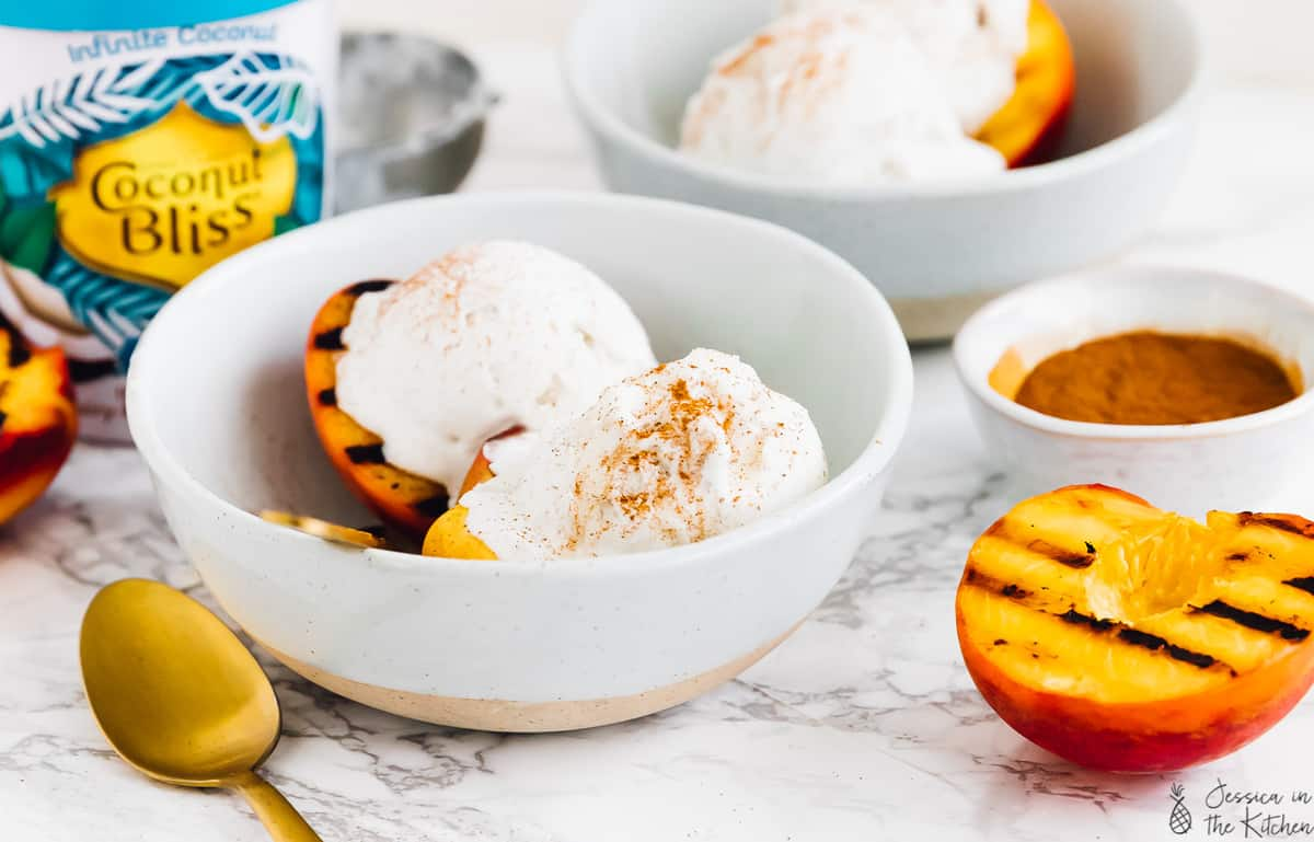 A bowl of grilled peaches topped with ice cream.