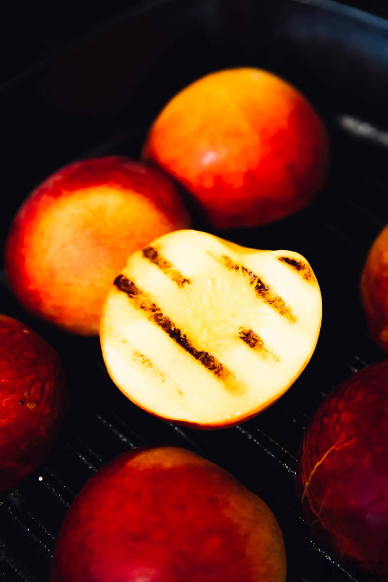 A grilled peach on a grill.