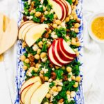 Top down view of kale, apple and vegan feta salad on a platter.