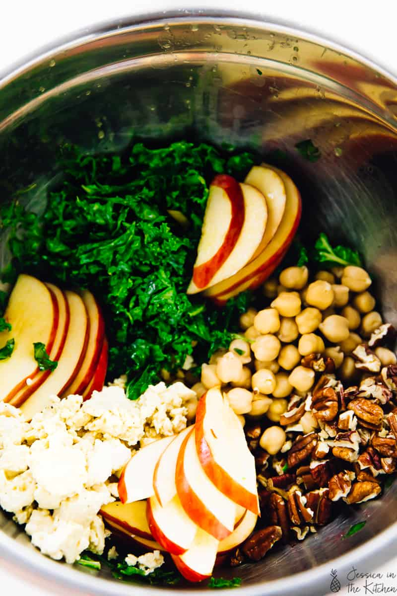 Sliced apples, chickpeas, vega feta and kale in a silver bowl.