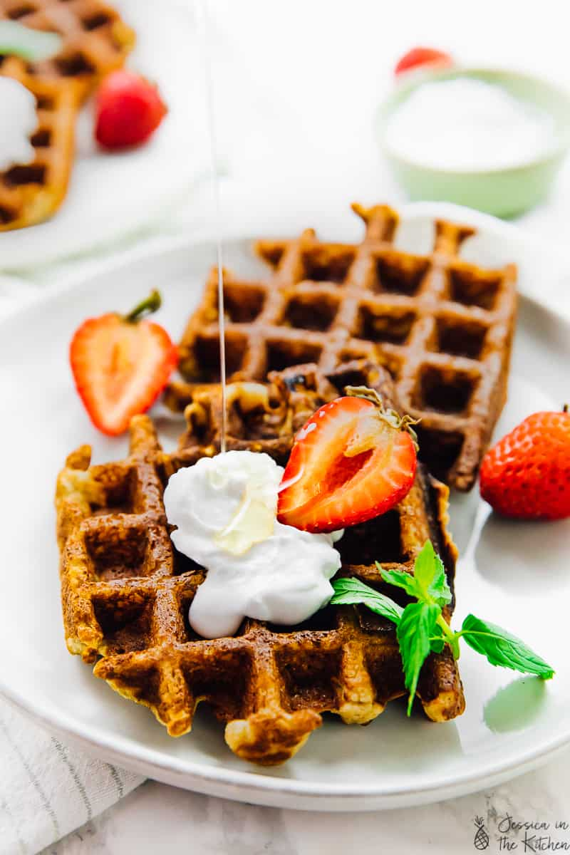 two low carb waffles with coconut whipped cream a strawberry and a mint leaf on a plate surrounded by strawberries
