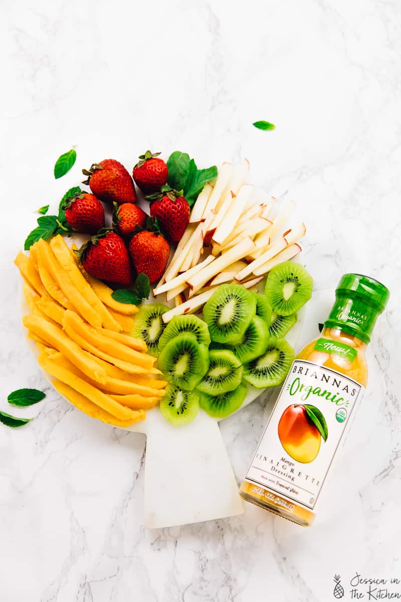 Overhead shot of sliced fruit and a bottle of dressing.