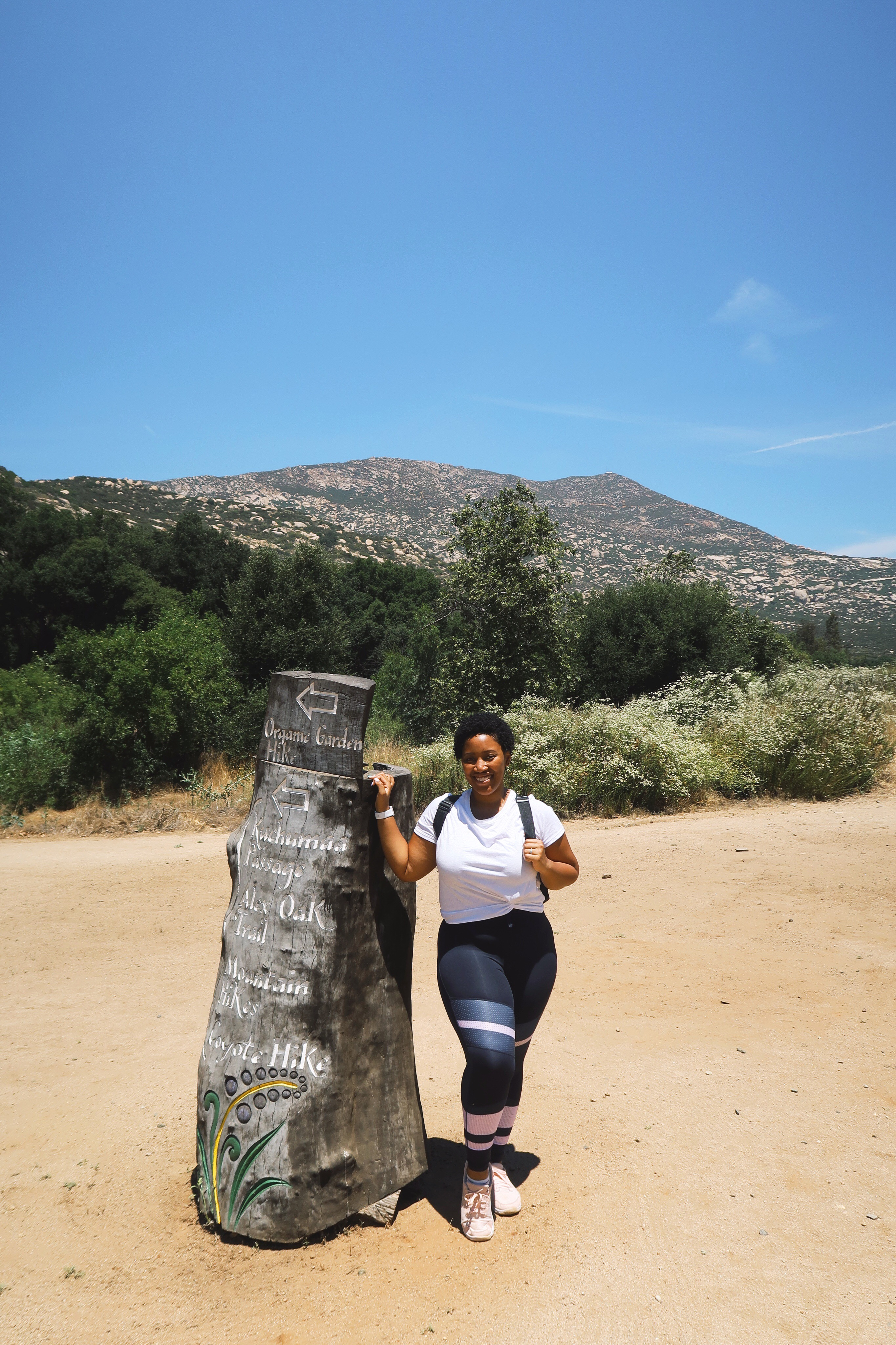 Jessica standing by a tree stump.