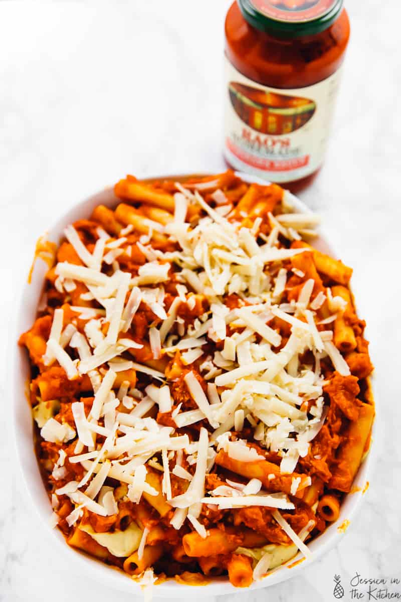 Pasta covered in tomato sauce and shredded cheese, in a baking dish.