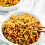 Vegan quinoa fried rice in chopsticks.