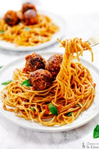A white plate of vegan spaghetti and meatballs with the spaghetti being pulled out with a fork.