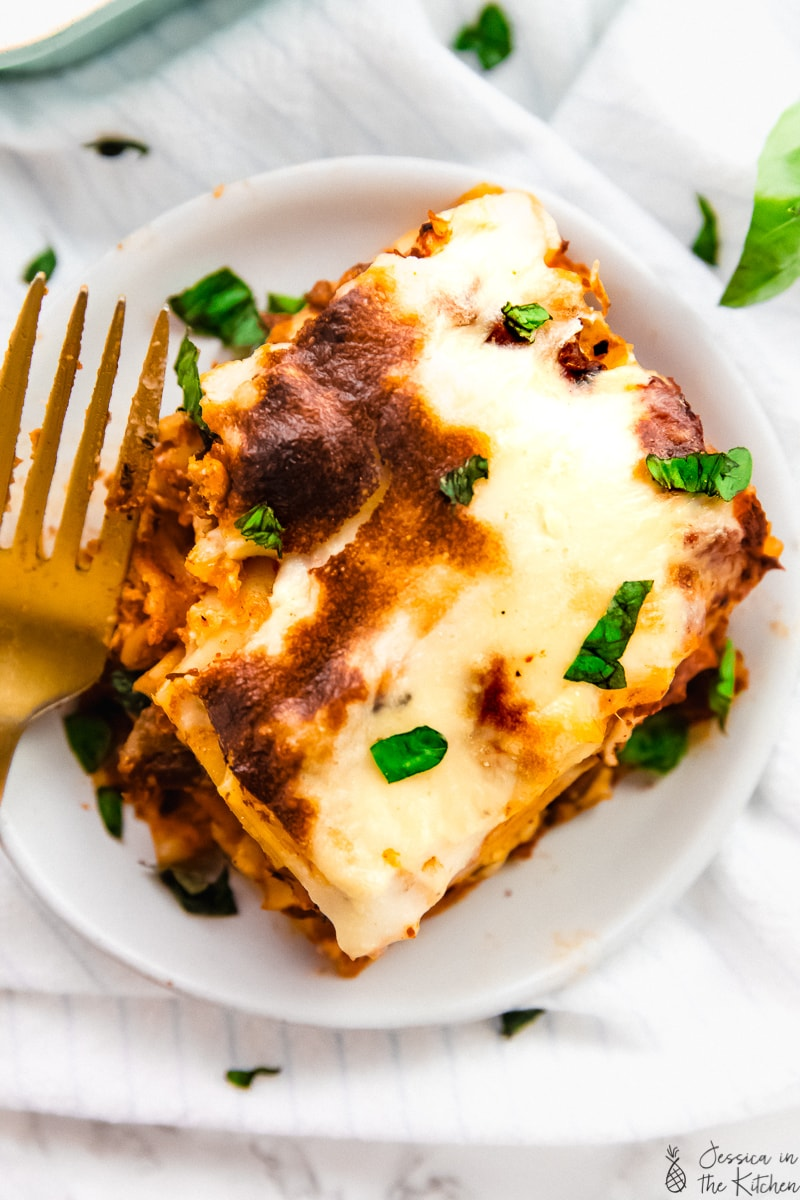 Overhead shot of a portion of vegan lasagna on a plate with a gold fork on the side.