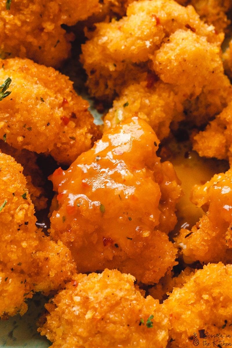 Close up of cauliflower wings with an orange mango sauce on them.