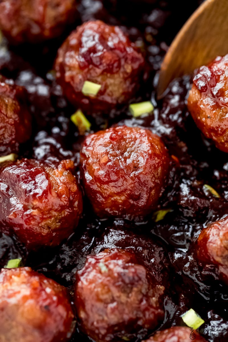 a close up of vegan meatballs covered in a cranberry sauce.