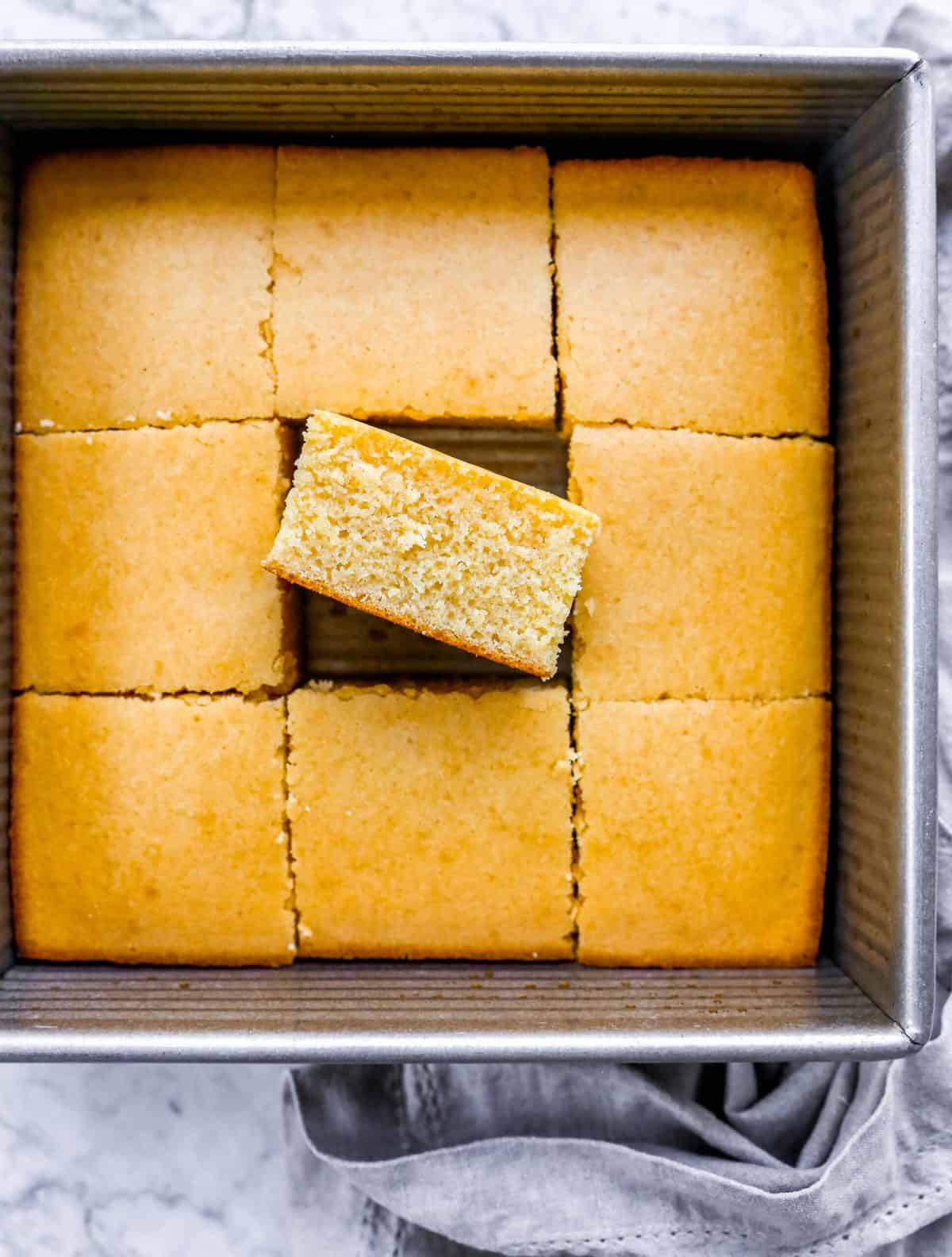 a pan of sliced cornbread with a fluffy slice on its side