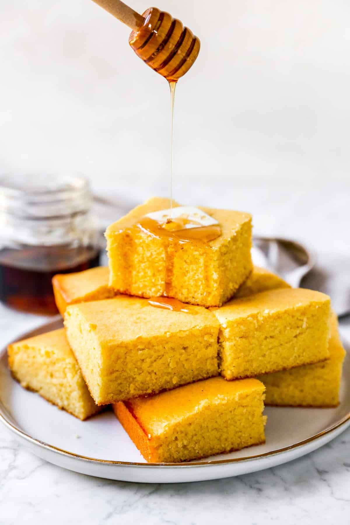 cornbread muffins in a stack with maple syrup drizzled on top and a pat of butter