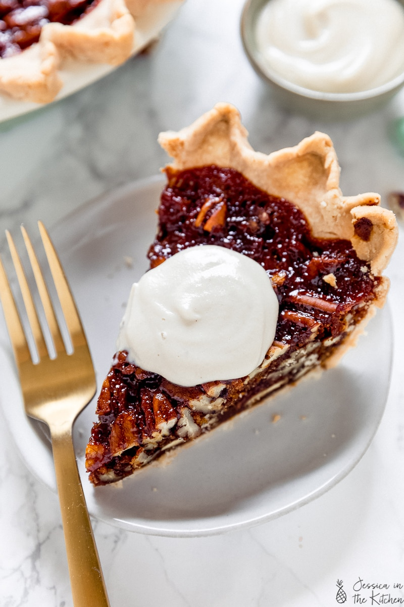 Cashew whipped cream on a slice of pecan pie.