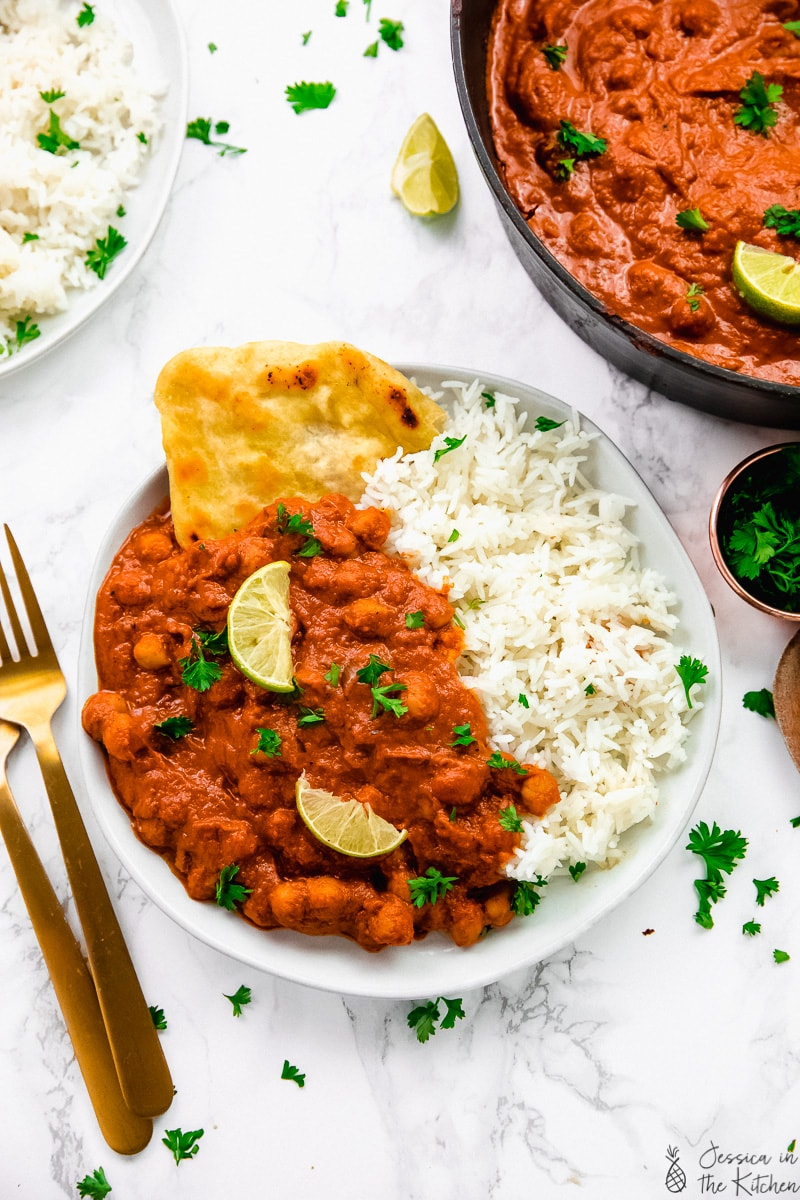 Chickpea tikka masala in a plate with rice and naan bread.
