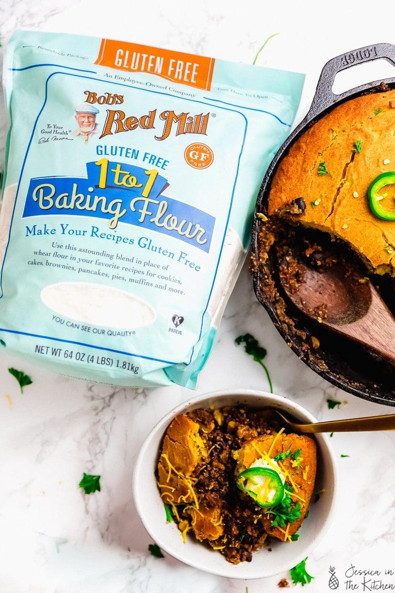 A pack of baking flour next to a bowl of cornbread casserole.