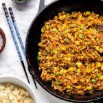 Vegan fried rice in a skillet, next to chopsticks.