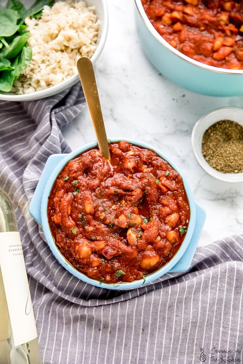 Top down view of creamy smoky white beans in garlicky tomato sauce in a blue pot.