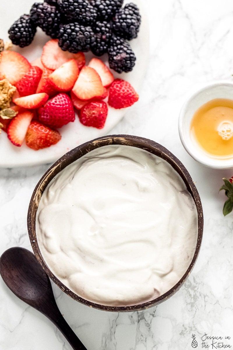 Top down shot of vegan yogurt in a brown bowl.
