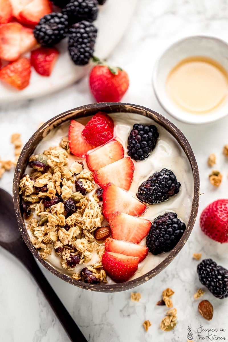 Vegan yogurt in a bowl, topped with berries and granola.